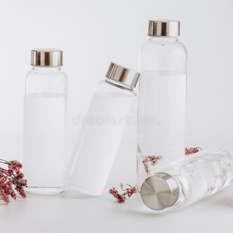 Frascos de água de vidro transparente sobre fundo cinzento brilhante Instagram Tonelado imagens de stock