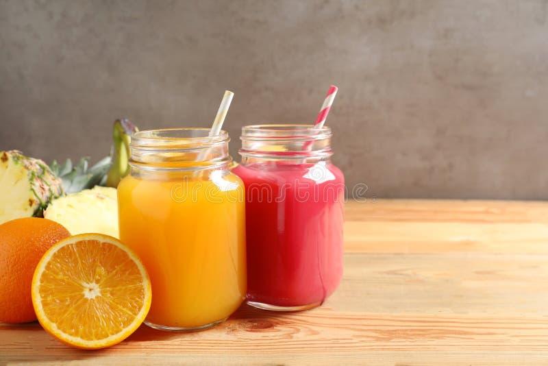 Frascos de pedreiro com sucos diferentes e frutos frescos na tabela de madeira contra o fundo da cor imagem de stock