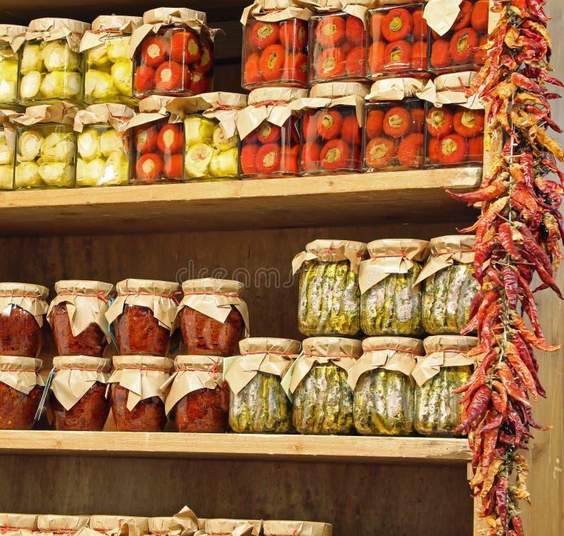 Frascos de vidro com alimento calabrês típico pimentas secadas do tomate e fotos de stock royalty free