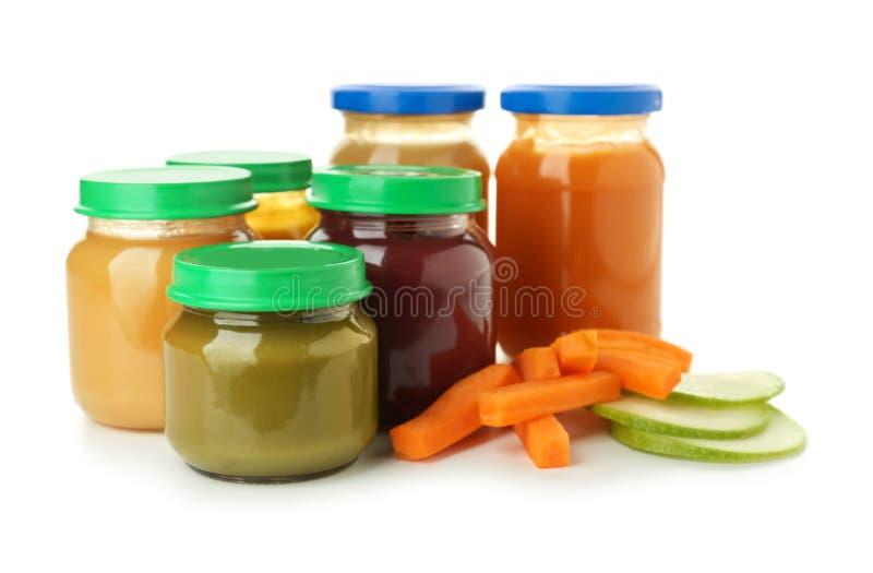 Frascos de vidro com comida para bebê saudável no fundo branco fotografia de stock