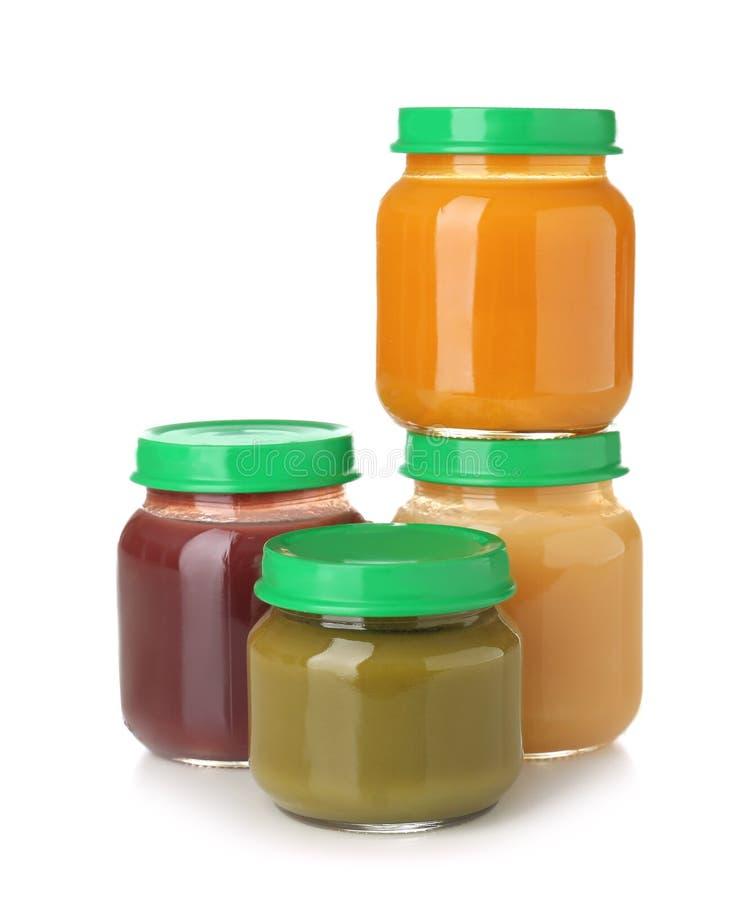 Frascos de vidro com comida para bebê saudável no fundo branco foto de stock