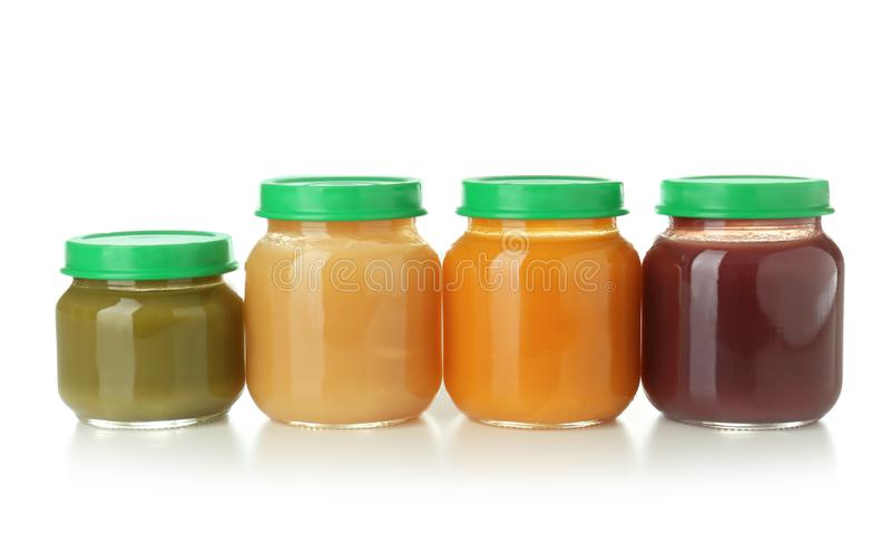 Frascos de vidro com comida para bebê saudável no fundo branco imagem de stock