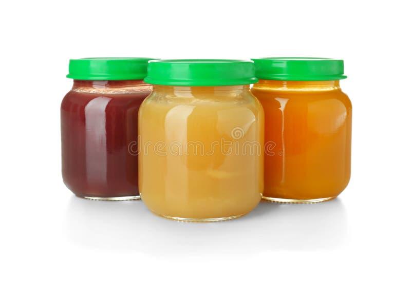 Frascos de vidro com comida para bebê saudável no fundo branco imagens de stock royalty free