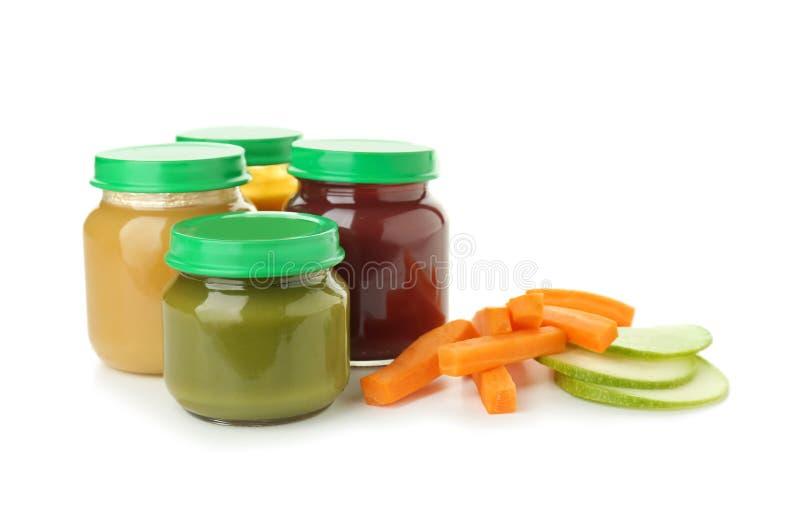 Frascos de vidro com comida para bebê saudável no fundo branco fotografia de stock royalty free