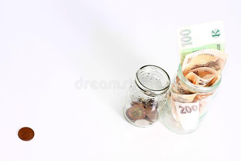 Frascos de vidro com moedas e cédulas imagens de stock