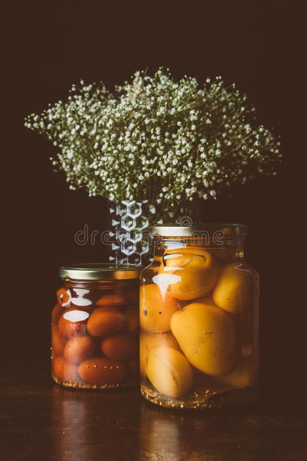 frascos de vidro com tomates e as flores preservados na tabela de madeira fotos de stock