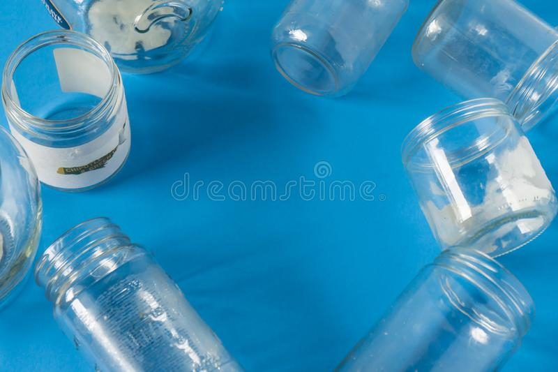 Frascos de vidro isolados sem tampas lisas no fundo azul com sala para o copyspace imagem de stock royalty free