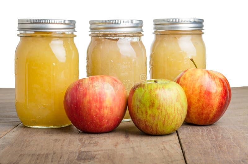 Frascos do molho de maçã com maçãs imagens de stock