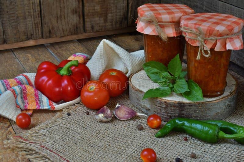 Frascos do molho de tomate com pimentão, pimenta e alho Molho, lecho ou adjika bolonhês preservação enlatar foto de stock