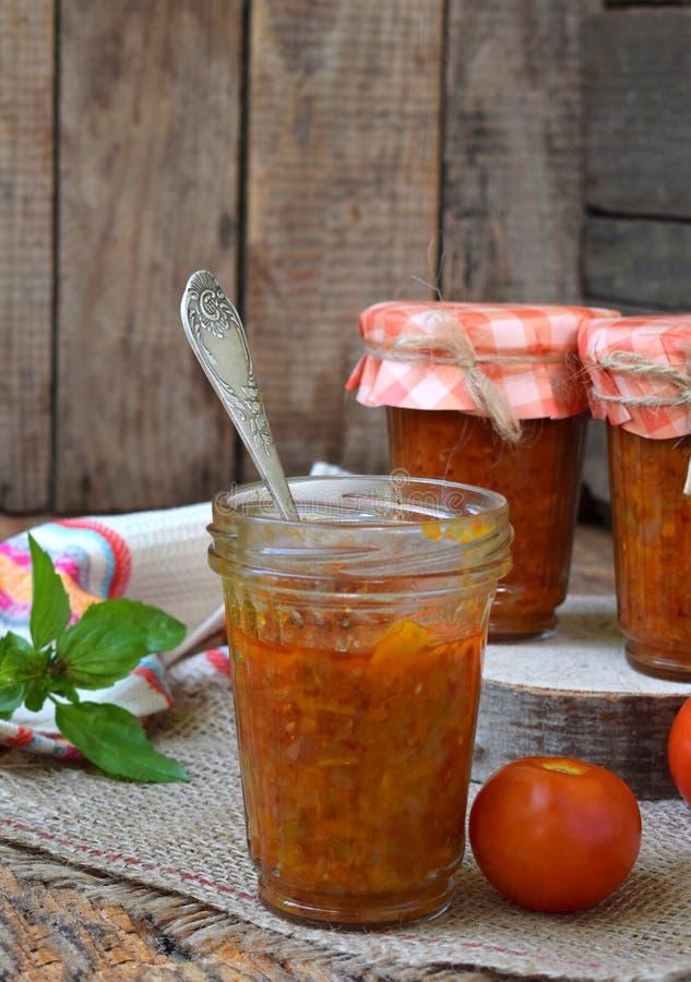 Frascos do molho de tomate com pimentão, pimenta e alho Molho, lecho ou adjika bolonhês preservação enlatar fotos de stock
