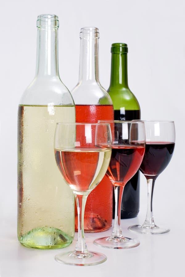 Frascos do vinho vermelho, branco e cor-de-rosa com vidros foto de stock