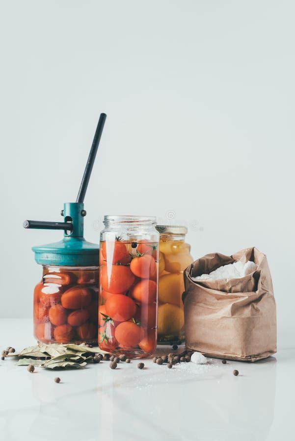 frascos e ferramenta de vidro para preservar tomates na tabela foto de stock