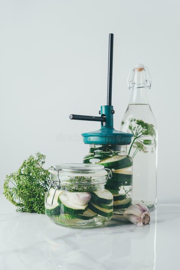 frascos e garrafa de vidro com abobrinha e aneto para preservar fotos de stock