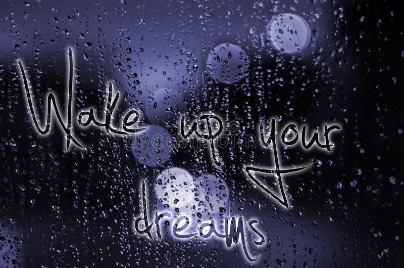 A frase acorda seus sonhos escritos em um vidro molhado Vida urbana da noite através do pára-brisas: escuridão e chuva foto de stock