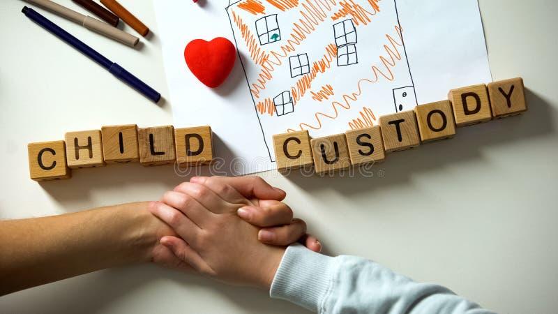 Frase de la custodia de los hijos y coraz?n del juguete en la imagen de la casa, mano de la madre de la tenencia del ni?o fotos de archivo libres de regalías