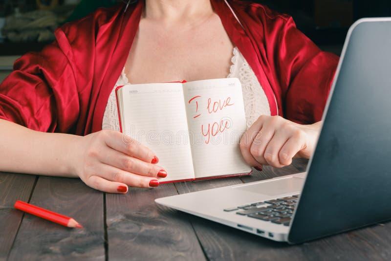 Frase de la demostración de la mujer te quiero al amigo en el webcam del ordenador portátil fotografía de archivo libre de regalías