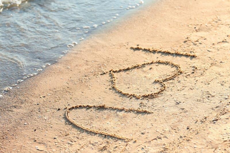Frase EU TE AMO escrita na areia da praia foto de stock