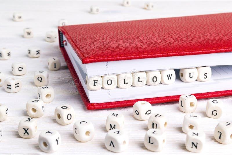A frase segue-nos escritos em blocos de madeira no caderno vermelho no whi foto de stock royalty free