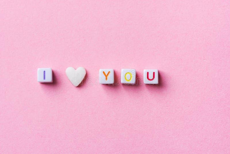 Frase te amo hecha de los cubos y de la sola forma Sugar Candy Sprinkle blanco de la letra del corazón en fondo rosado Tarjetas d foto de archivo libre de regalías