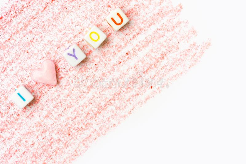 Frase ti amo costruita dai cubi bianchi della lettera e dallo zucchero candito rosa di forma del cuore sul fondo rosso dei colpi  fotografie stock