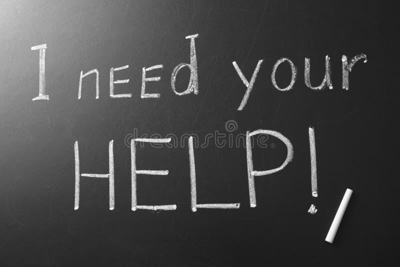 Fraseie-me 'precisam sua ajuda 'escrita no quadro imagem de stock royalty free