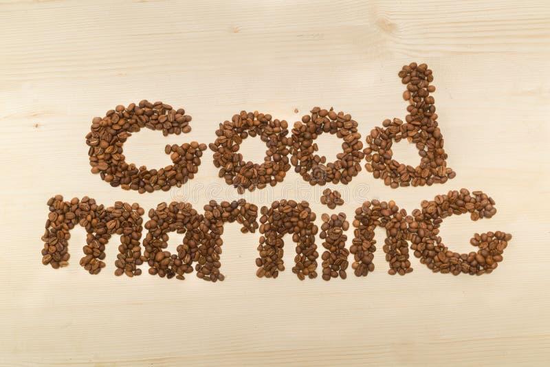 Fraseie o bom dia feito com feijões de café em uma opinião de tampo da mesa ilustração stock