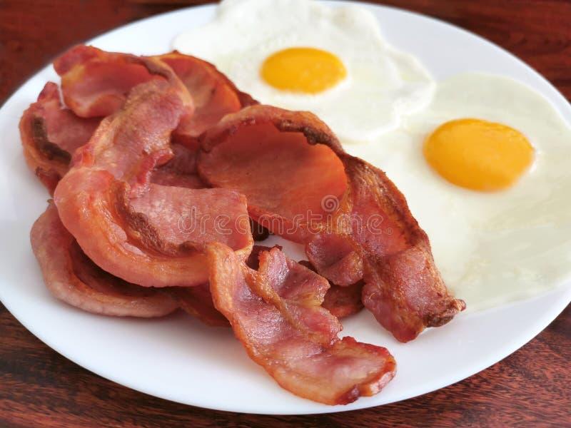 Frasig bacon med ägg i en vit platta på trätabellen arkivbild