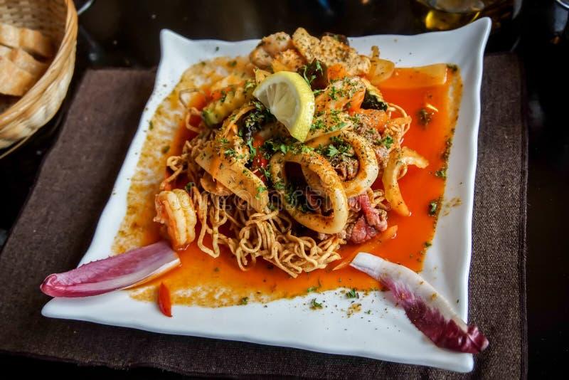 Frasig kinesisk nudelmaträtt med skaldjur, fisk, räka, tioarmad bläckfisk arkivbild