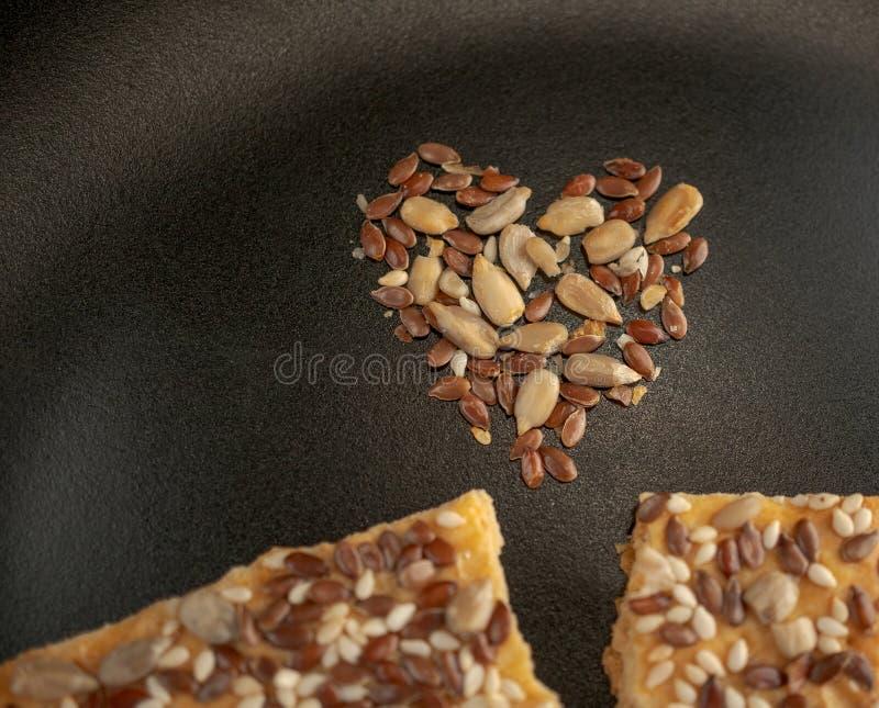Frasiga kakor för strikt vegetarian med solrosen, linfrö och isolerat sesamfrö royaltyfri bild