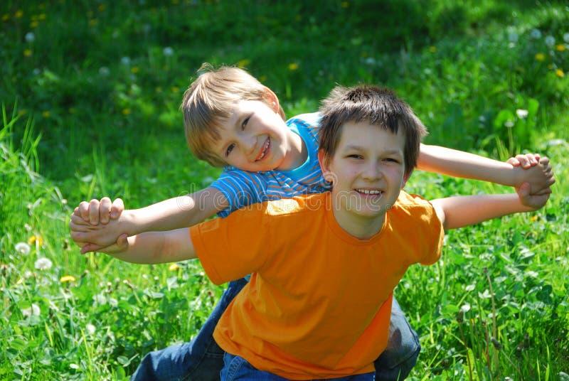Fratelli che giocano nel prato fotografie stock