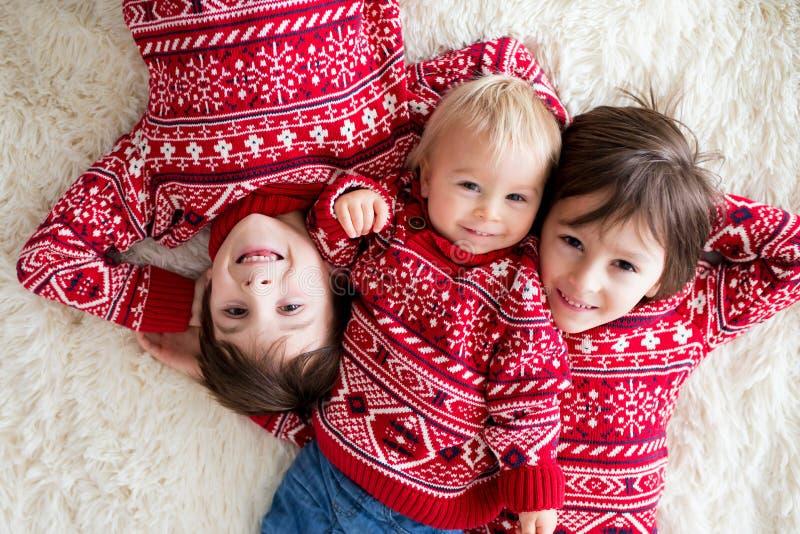 Fratelli felici, bambino e bambini in età prescolare, abbracciando a casa sulla coperta bianca, sorridente fotografie stock