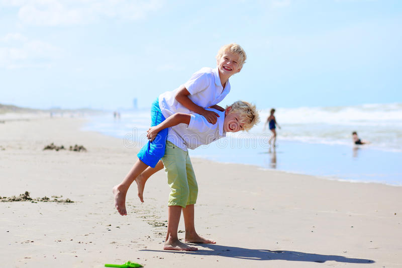 Fratelli gemelli che giocano sulla spiaggia immagine stock
