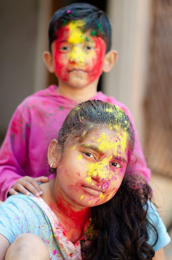 Fratelli germani adorabili svegli che giocano con i colori durante il festival di holi del ritratto creativo caucasico asiatico i immagine stock