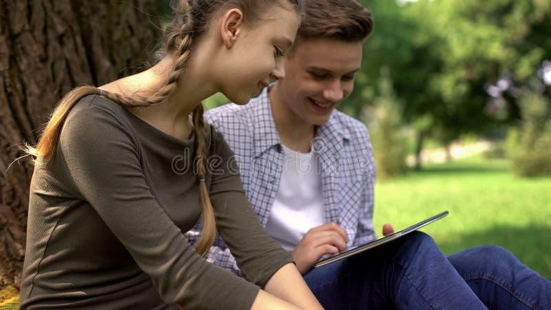 Fratelli germani amichevoli che fanno scorrere le pagine sulla compressa, sulle reti sociali e sui giochi online immagine stock libera da diritti