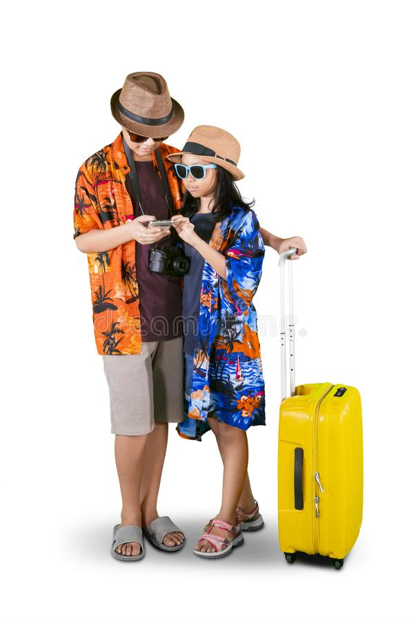 Fratelli germani asiatici con il telefono ed i bagagli sullo studio fotografia stock