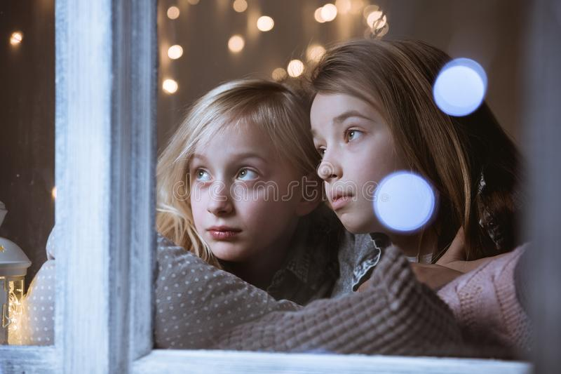 Fratelli germani che guardano fuori la finestra fotografia stock