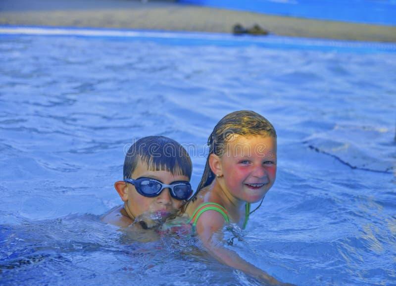 Fratelli germani, piccola ragazza e ragazzo nella piscina il giorno di estate Estate e concetto felice di infanzia Copi lo spazio fotografia stock