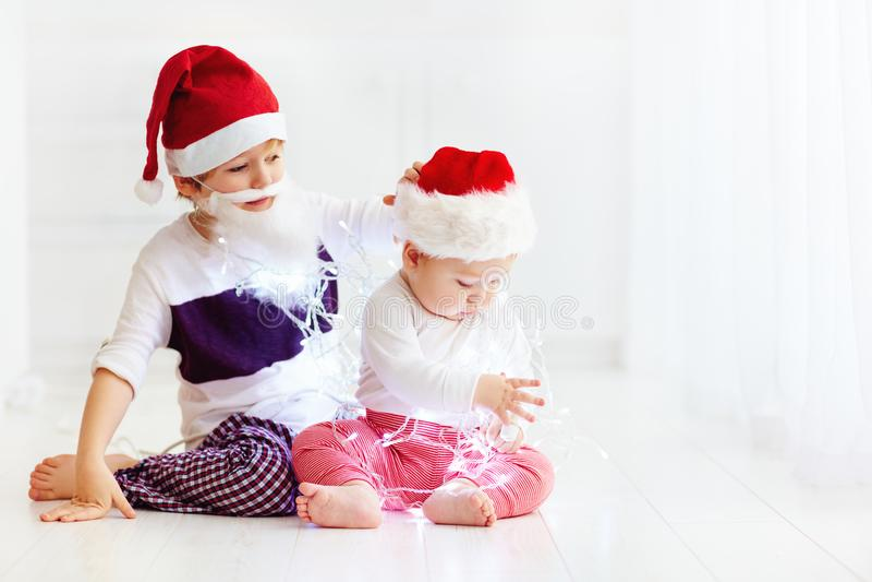 Fratelli germani svegli del fratello, bambini in cappelli del ` s di Santa e ghirlanda che gioca a casa fotografia stock libera da diritti