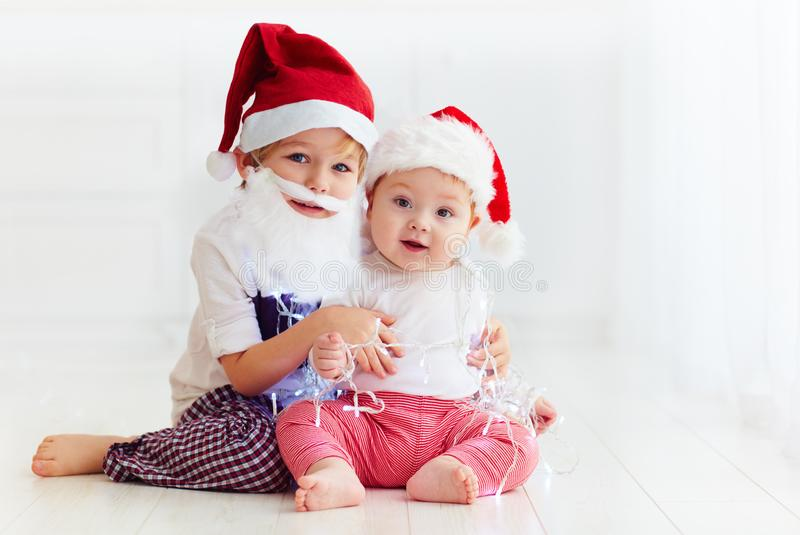 Fratelli germani svegli del fratello, bambini in cappelli del ` s di Santa e ghirlanda che gioca a casa fotografia stock