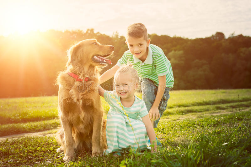 Fratello adorabile e sorella che giocano con il loro cane immagini stock