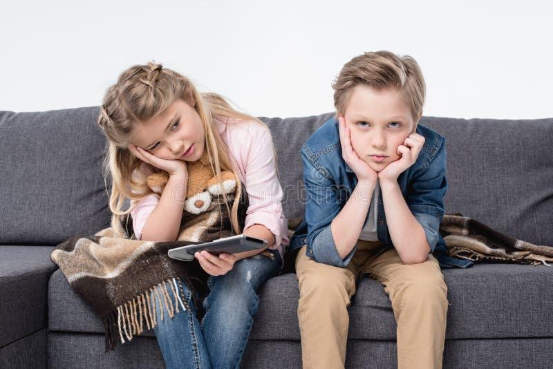 Fratello annoiato e sorella che si siedono sul sofà e che tengono telecomando immagine stock