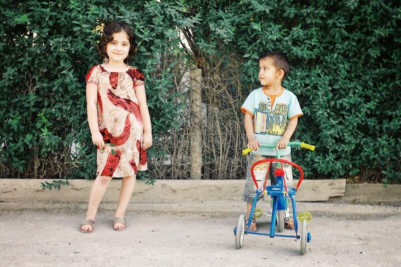 Fratello e sorella che giocano con un triciclo in vestito tradizionale sveglio immagini stock
