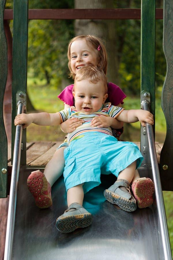 Fratello e sorella che giocano sul campo da giuoco fotografia stock