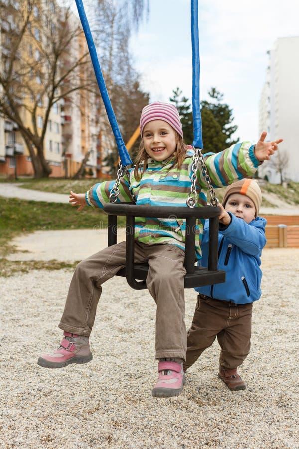 Fratello e sorella che giocano sull'oscillazione fotografia stock