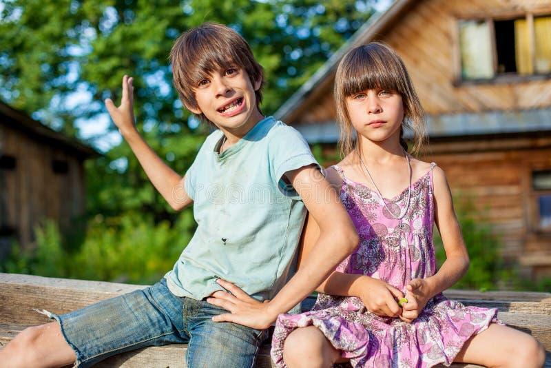 Fratello e sorella che si siedono su un banco nel villaggio immagini stock libere da diritti