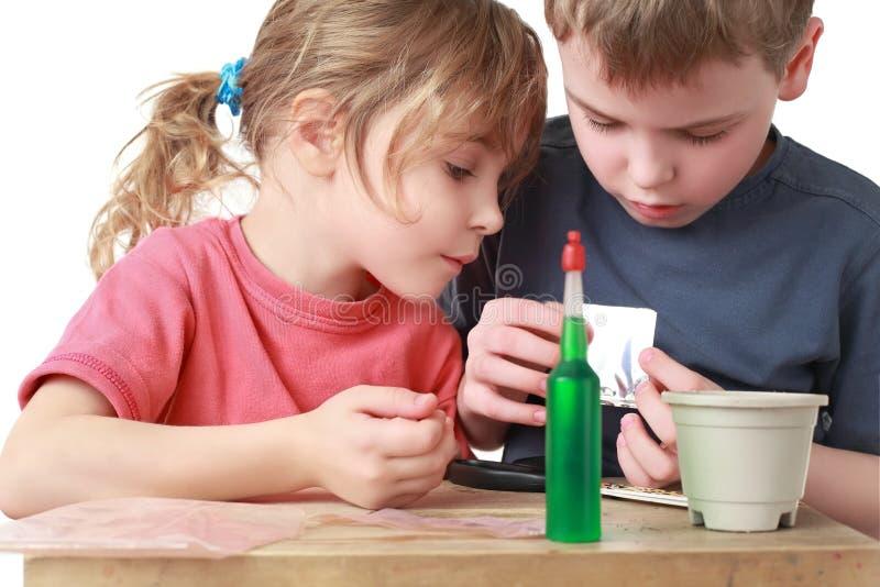 Fratello e sorella che vanno mettere i granuli a sedere in POT fotografia stock