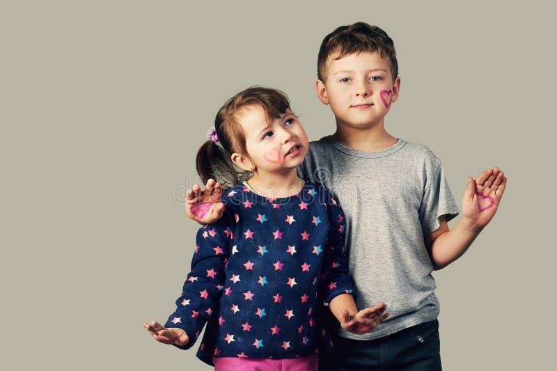 Fratello e sorella con i cuori dipinti sul viso e sulle mani fotografie stock