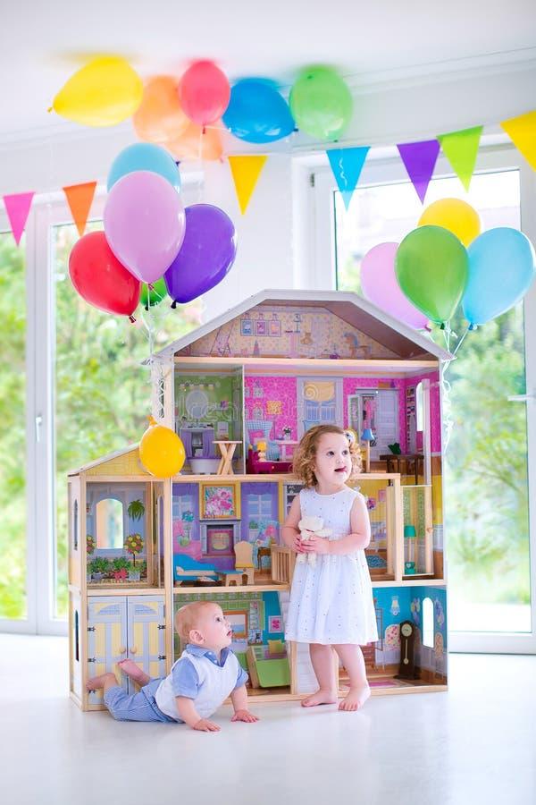 Fratello e sorella del bambino che giocano con una casa di bambola fotografia stock libera da diritti