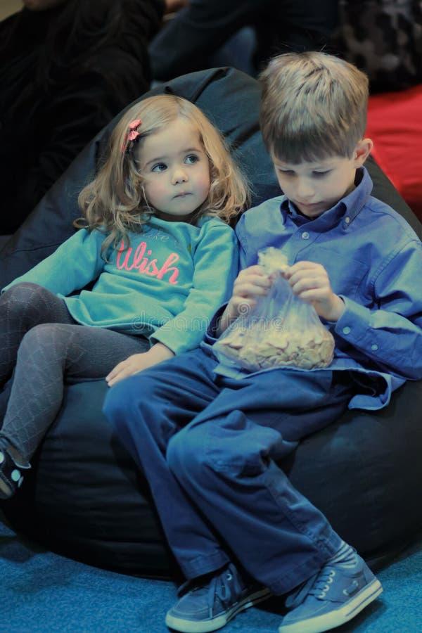 Fratello e sorella, ragazzo e ragazza, dividenti beanbag molle nel cinema del bambino fotografia stock libera da diritti