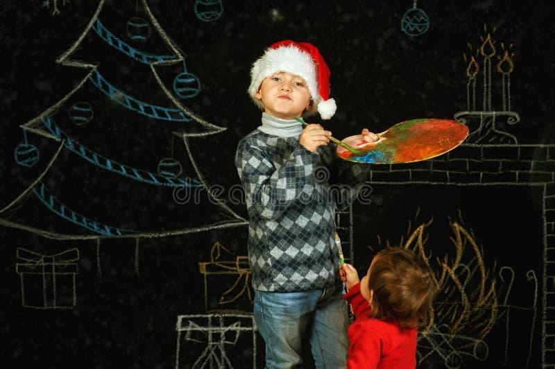 Fratello e sorella sul fondo di Natale, giocando con una tavolozza e le spazzole Buon Natale fotografia stock libera da diritti